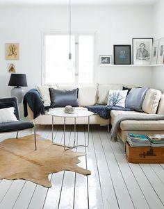Avonaisen tilan toinen puoli on oleskelutilaa. Lehmäntalja löytyi Iskusta. Italialainen nojatuoli on ostettu Varistosta Inside.fi-liikkeestä ja sohva Kruunukalusteesta. Pyöreä sohvapöytä on BoConceptin mallistosta.