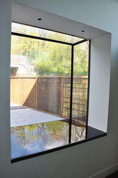 A frameless glass window seat with black back painted glass base