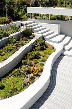Bettys Bay Retreat by Sarah Calburn Architects Sloped Backyard Landscaping, Backyard Retaining Walls, Concrete Retaining Walls, Sloped Garden, Landscaping Ideas, Concrete Patio, Hillside Garden, Terrace Garden, Garden Seating