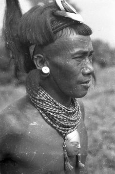 India | Mewang, Ang of Chi. Wearing a brass-head chest ornament, a decorated hat with wild boar tusks, a hairpin and earplugs. Around his arms he wears ivory armlets. Wakching, Nagaland, Mon District. 1936. | ©SOAS, Nicholas Haimendorf