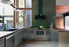Stainless steel cabinets with green tiling.