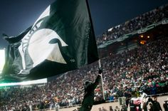 The MSU Cheerleading team runs a flag across the endzone after a Spartan touchdown during the game against Michigan, Nov. 2, 2013, at Spartan Stadium. MSU defeated the Wolverines, 29-6. Danyelle Morrow/The State News