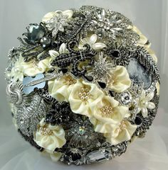 A fabulously unique bouquet in antique silver, black and ivory colors. This beautiful handmade heirloom bridal hbouquet is perfect for a stylishly chic wedding ~ from Formal, Vintage, or Antique to even Gothic. The elegantly wrapped handle is accented with a black jewel. The design and craftsmanship is unmatchable and will definitely make your wedding day both Extraordinary and the Talk of the Town... Made with brooches, pendants, bracelet, rings, earrings and jewels.