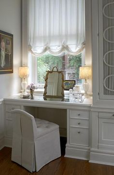 Elegant dressing room features a mirrored top makeup vanity, placed under window dressed in a white ruched shade, topped with a gold tasseled mirror paired with a tufted vanity stool.