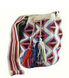 Bolso tejido a mano por la comunidad indígena Wayúu, que habita en la península de la Guajira en Colombia. Tejer significa para los Wayúu mostrar a través de su creatividad, inteligencia y sabiduría su forma de vida, representada a través de figuras geométricas que simbolizan elementos de la naturaleza que rodean su vida cotidiana.