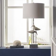 Bring a soothing, coastal vibe to your space with this distressed Seagull table lamp by Surya (SGLP-001).