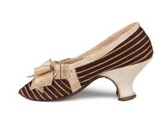 Striped silk Louis heel shoes, c.1750s, decorated with a bow on the vamp.  Ladies dark lilac silk shoes with red and yellow stripes. Vamp is decorated with ecru silk bow. Edge piping is of the same silk, pleated at the vamp throat. Lining of the vamp - linen, quarters are lined with cream kid leather.