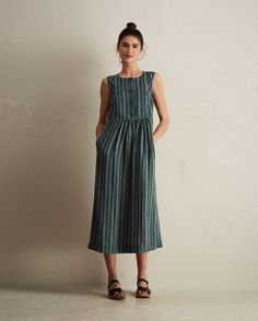 Supple, midweight, indigo-dyed linen with a woven, yarn-dyed ticking stripe. Bib front with four button placket. Gathers into waist seam. Concealed side zip. Cotton facings. Pockets.