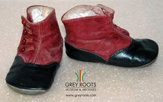 A pair of small child's dyed-red and black leather boots. To fasten, the shoes have 4 red buttons on the outer side of the ankle. Grey Roots Museum & Archives Collection.