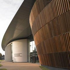 A slatted timber concert hall bulges through the glass atrium walls of this performing arts college in Cardiff