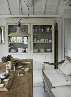 Charming French farmhouse kitchen eating area with farm table, antique hutch, farmhouse bench, and industrial light. French Farmhouse Decor Inspiration Ideas will take you on a romantic tour of images capturing this charming decor style. French Farmhouse, Farmhouse Table, French Country, Rustic Table, French Style, Rustic French, Farmhouse Decor, Rustic Dining Rooms, Modern Rustic