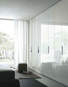 Glatte weiße Türen mit Griffen sehen glänzend aus und reflektieren das natürliche Licht, wodurch der Raum größer wird