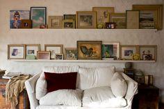 Unos cuadros apoyados en estanterías pueden ayudarnos a decorar una pared del salón ...