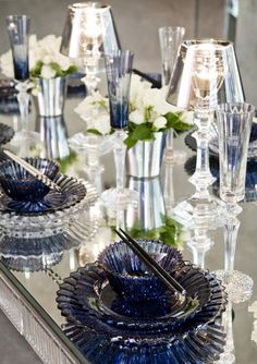 Gorgeous mirrored dinner table with blue colored glass and crystal. Such an elegant affair. Use Candle Impressions LED candles in those holders to keep them pristine.