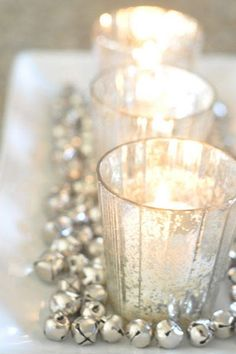 Create a chic holiday centerpiece by surrounding candles with silver jingle bells.    - HarpersBAZAAR.com