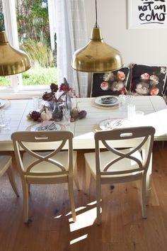 Esszimmer Deko für den Herbst mit Natur und hellen Tönen. Interior, Dekoration. Naturdeko mit Artischocke, Pfefferbeere und Kürbis auf dem Tisch