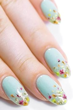 Tiny Dried Petals Instead of painting on flowers, why not apply actual petals? In this Ipsy manicure, Nail artist Kristin Gardner attached tiny dried blooms to a glitter-ombre base.