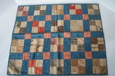 Pat Hatch:* 19th C. early patchwork doll quilt  blue calico back with nice early calico fabrics. It is hand sewn and has the best solid blue calico back. It has a number of weak squares that are shredding and half missing, so the quilt is as is but is so good looking hanging or folded in a stack it is hard to resist. Circa 1870-80