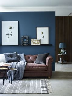 Chic Seating Area With A Brown Sofa And Navy Accent Wall Textiles Blue