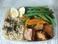 Hard boiled egg, brown rice with black sesame seeds, blanched carrots and beans, and deep fried tofu with green onions and oyster sauce.