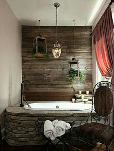 A bathroom with a massive stone hot tub set against all wood walls.