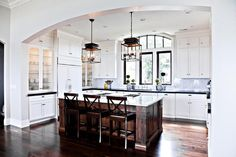 Stunning U shaped kitchen features white cabinets paired with black granite ocuntertops and a marble subway tile backsplash.