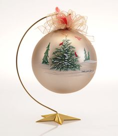 "Hand painted Christmas heirloom, 7"" in diameter, brass stand is 12"" tall, Swarovski Crystals at the top of tree and at the center of each delicate snowflake scatter around the orb. 4.25 "", 6"" and 7"" available in many designs. http://mickeybaxterspade.com/christmas-ornaments/"