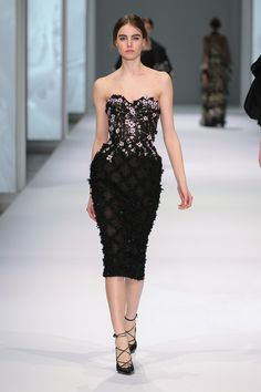Black silk organza dress with lace crosshatch appliqué and metallic thread-work bustier, with leather flower appliqué.