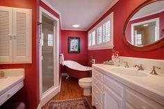 salle de bains avec une peinture murale rouge, baignoire en blanc et rouge et meuble sous-vasque blanc