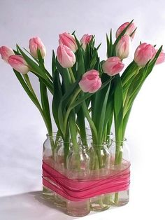 Pink tulips in recycled starbucks frappacino bottles. Tie with burlap or something similar