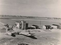 """The RAF Molesworth control tower in April 1944. On the taxiway is a B-17G, tail number 42-97284 """"Ain't Misbehavin"""" – she would fly a total of 48 combat missions during the war. The """"Triangle-C"""" marking on the verticle stabilizer was the RAF Molesworth designator. The Class A Airfield imporvements: three converging airstrips with a concrete runway of at least 6,000 feet are visible in the distance. Photograph by Mr. Milton """"Chic"""" Cantor, the photographer of the 303rd BG(H), with thanks to the…"""