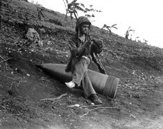 American GI checks his boots sitting on unexploded 406-mm (16 inches) shell from a US naval gun at an unidentified Pacific War battlefield.