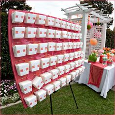 To create a unique display for the candy buffet favor boxes, we covered a cork board in fabric (that matched the table runners) and pinned the boxes on with rhinestone-adorned pushpins.