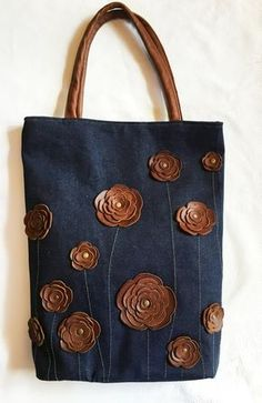 A truly cheerful and spacious bag for all activities. Ideally spacious to fit all your necessary things. This roomy tote bag has made from blue denim canvas and dark chocloate brown leather leather (flowers, handles). In front of the bag there are assortment of flower ornaments made of genuine leather and sewn to a bag, finally adorned with antique golden rivets.  Measurements: 14,5 x 17 (36,5 x 43,5 cm), bottom 3 x 11,5 (6,5 x 28 cm). Two interior pockets and one zippered pocket…
