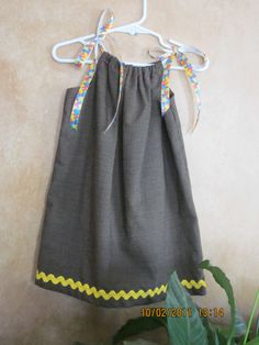 This little girl's dress of black homespun is made from the pillow case pattern. Yellow rick rack trim, and brightly colored ribbon ties. Pair with a turtle neck, and leggings and she's off for a fun day at school. Size 3-4 $18 plus s/h
