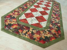 Autumn Table Runner is made with these beautiful fall fabrics in brown, green, rust and gold bordered and backed with green fabric that has leaves