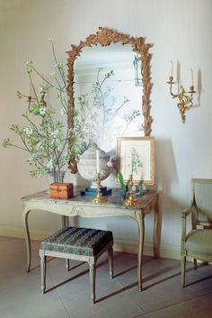 Deed Blair: A stone urn and an 18th-century French gilded mirror adorn a marble-topped table in the entry hall.