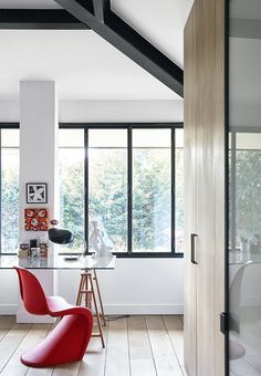 Bright and open home office with a glass table and a red Verner Panton chair.