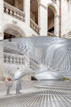 FAKT hovers an undulating aluminium cloudscape within a french courtyard