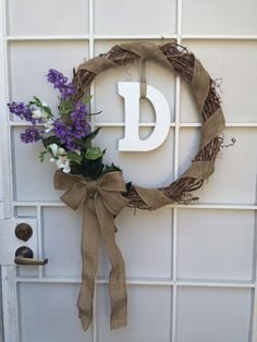 Handmade wreath for my front door. Woven grape vine wreath with burlap ribbon, flowers, and wooden letter.