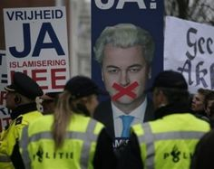 """Supporters of Geert Wilders hold banners reading """"Freedom Yes, Islamisation No"""""""