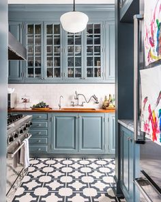 Blue cabinets, gray and white tile floor in kitchen