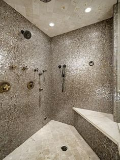 Large  multi person shower with walls covered in tiny sparkly tiles and built in bench and gold hardware