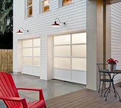 Modern glass garage doors look right at home on this contemporary farmhouse in FL. The red gooseneck lamps add fun color. Clopay Avante Collection garage doors, white aluminum frame with frosted glass and solid aluminum panel design. White Garage Doors, Garage Door Colors, Garage Door Windows, Modern Garage Doors, Garage Door Styles, Glass Garage Door, Garage Door Design, Contemporary Garage Doors, Glass Doors