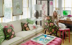Brow, Pink & Green Living Room with pink tufted ottoman, cream couch with lime green piping, flowered and zebra-print accent pillows and botanical prints hung over windows - Liz Caan via Attention to Detail