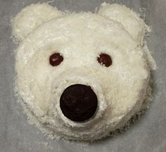 """Polar Bear Cake. No recipe with this but-an 8"""" round pound cake,cupcake snout, buttercream frosting, coconut on top then a choc covered oreo for the nose and choc candy for the eyes. Oh, and cut a cupcake in half for the 2 ears. Job done!"""
