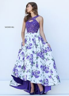 The Sherri Hill 50481 prom dress is a beautiful way to rock the floral trend. Featuring a lace bodice on a floral skirt, the skirt is lined with matching fabric in a solid color. The top has a halter neckline with lace straps that kiss in the middle to create a keyhole over the decollete. Front pockets are hidden within the gathers of the skirt as it falls to a tapered high-low hem, to reveal a peek at your shoes. The backline comes to a point with a center back zipper and lace straps to…