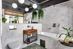 Gravity Home: Bathroom with plants in an Industrial Apartment That Looks Bigger With A Simple Trick