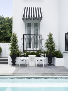 Black And White Greek Key Pool Tile, Black And White Striped Awning And Chairs, And Topiaries With Matte Black Planters