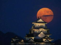 Red moon over a Castle in Japan